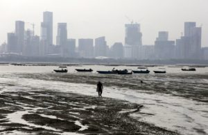 A man walks during low tide at Lau Fau Shan, famous for its oyster culture, in Hong Kong's rural New Territories July 3, 2015. The fast developing city of Shenzhen on mainland China is seen in the background. REUTERS/Bobby Yip - RTX1IXIL